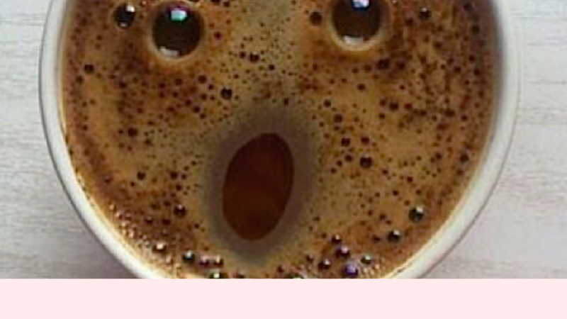 Cup of black coffee with face in the foam