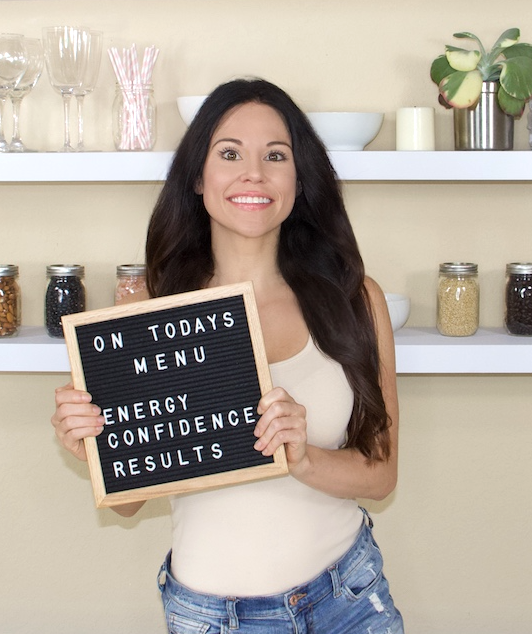 Nutritionist & Fitness Trainer Christina Carlyle with a signs that says on today's menu energy confidence and results