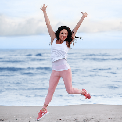 Christina Carlyle jumping at the beach