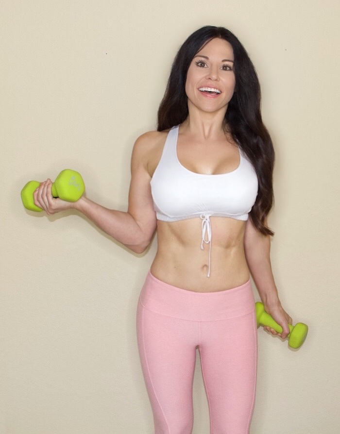 Trainer & Nutritionist Christina Carlyle posing with weights